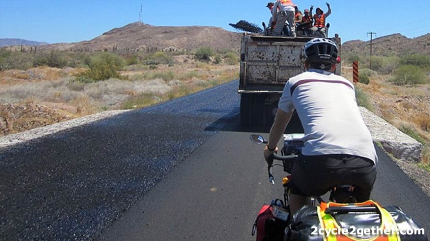 Road workers laying asphalt (and throwing peace signs) on a highway in Baja.